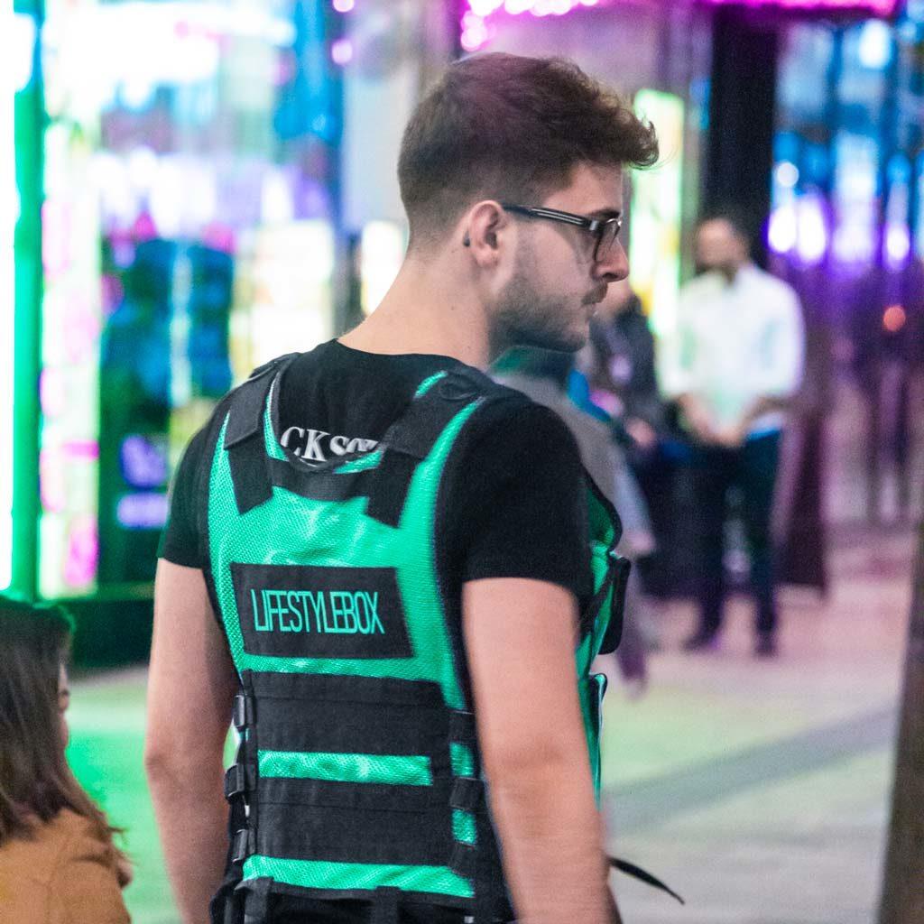 Chris Pollak der Gründer von Lifestylebox in der Fußgängerzone mit einer grünen Lifestylebox Veste vor einem farbenfrohen Hintergrund.