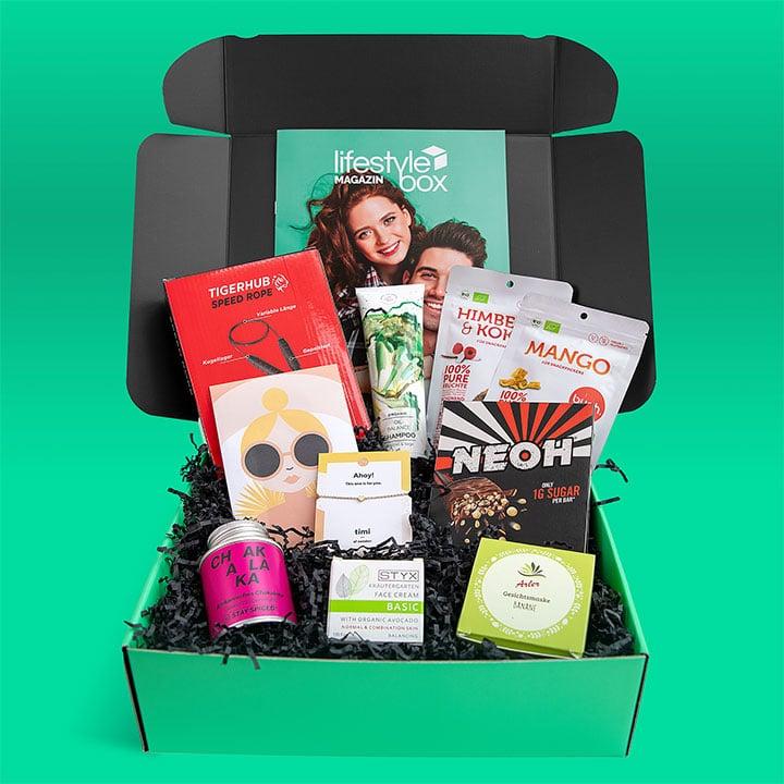 Die Lifestylebox April 2020 Ausgabe steht vor einem knallgrünen Hintergrund, die enthaltenen Produkte sind von Stay Spiced, Styx, Arler, Timi of Sweden, Neoh, Tigerhub, Hands on Veggies und buah.