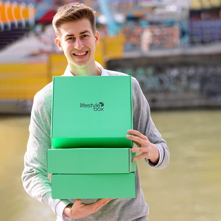 Moritz Lechner lächelt mit drei Lifestyleboxen in den Armen.