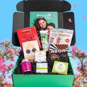 Die Lifestylebox April Ausgabe mit einem Gesamtwert von über 115 Euro vor einem frühlingshaften Hintergrund.